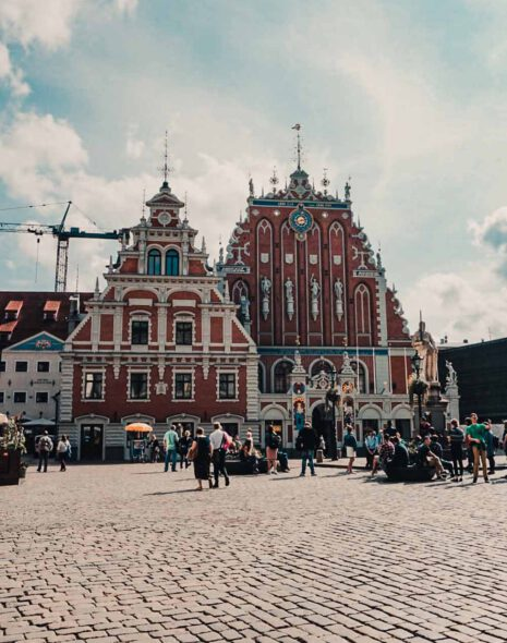 Picture of the House of the Blackheads in Riga, Latvia. It has a brownish facade with white details. It also has a blue clock and is decorated with four statues