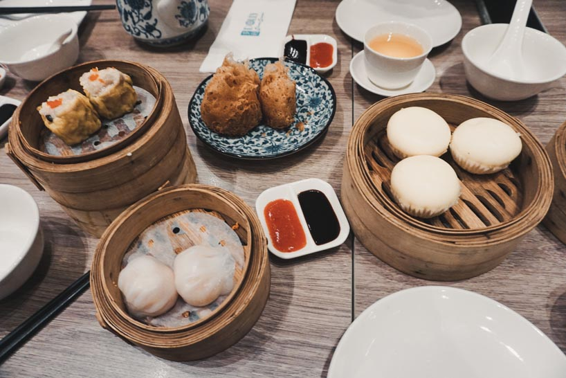 A table illed with a lot of plates with Dim Sum.