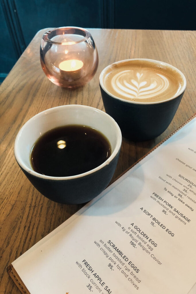 A wooden plate, with a candle, two coffees