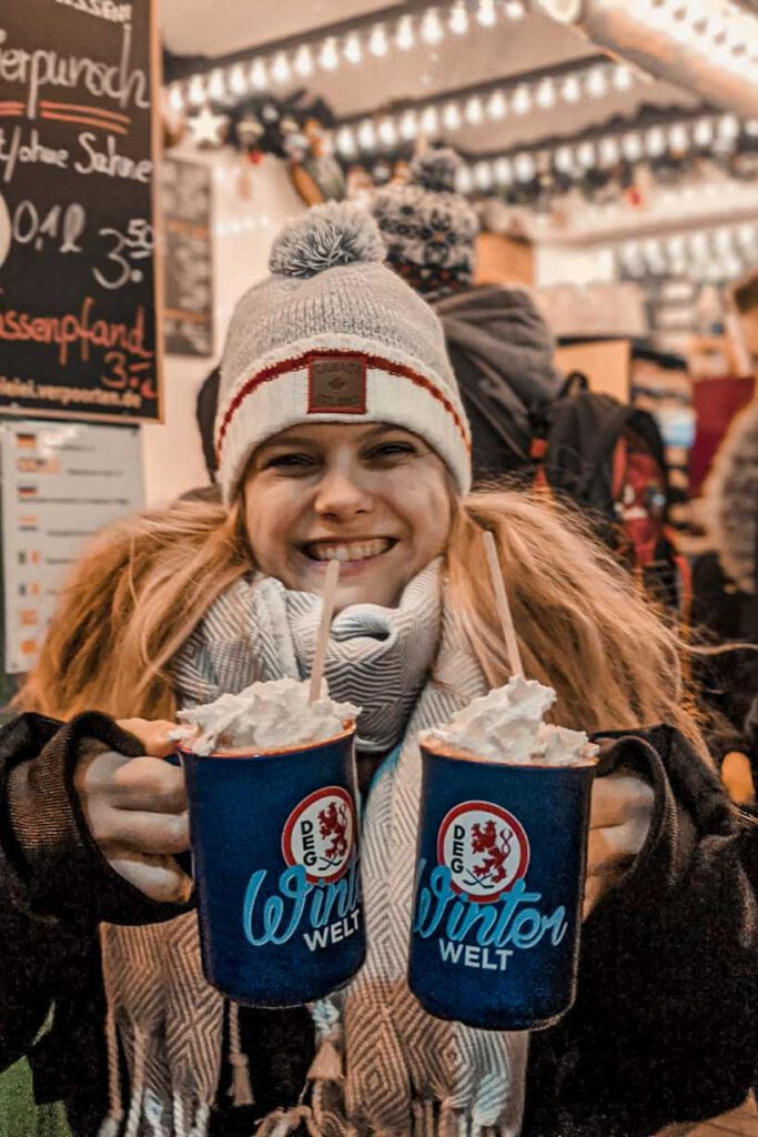 A girl holding two cups with hot chocolate and cream at the Christmas Market at Königsallee