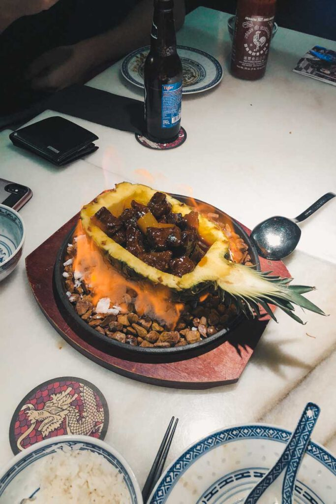 a burning pineapple with meat in it