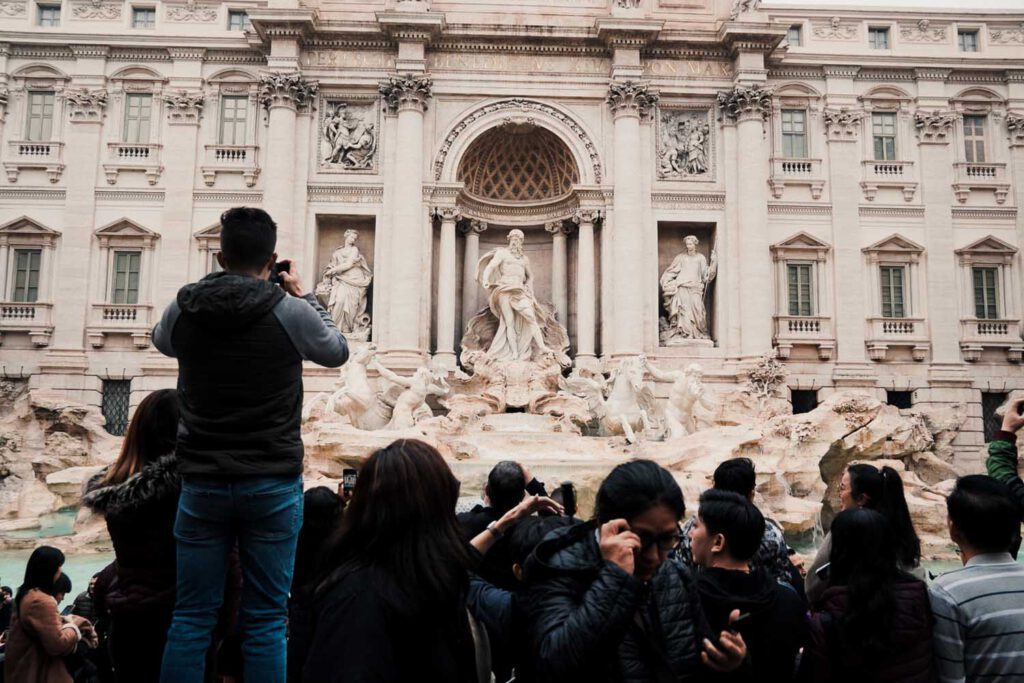 crowds standing in front of Trevi Fountain