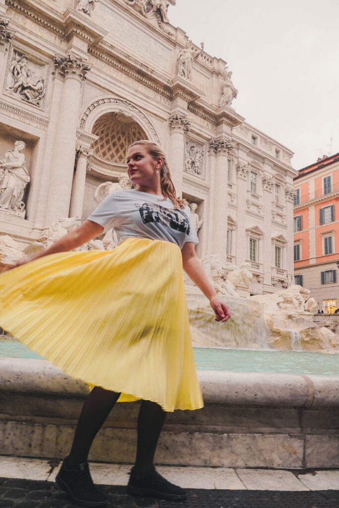 girl with yellow skirt in front of Trevi Fountain