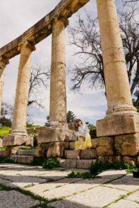 Girl sitting between some pillars in Jerash, Jordan