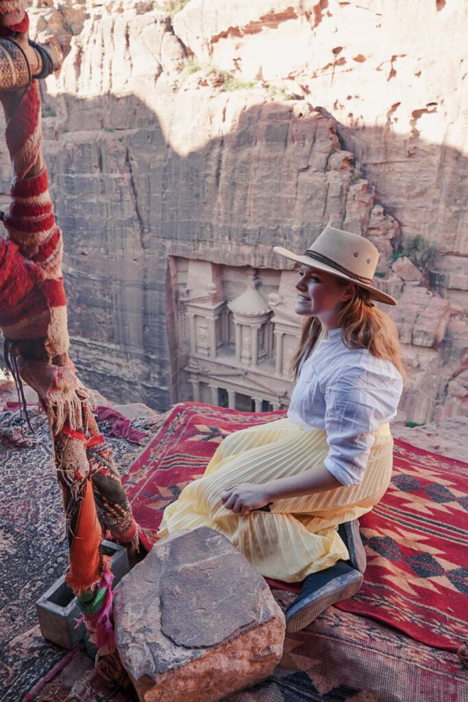 Girl, sitting on an edge, watching above the Treasury of Petra