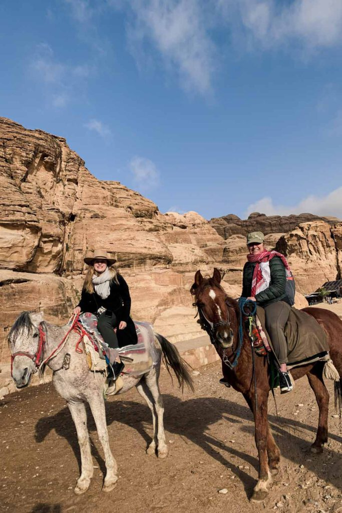 Women sitting on two horses, riding into Petra