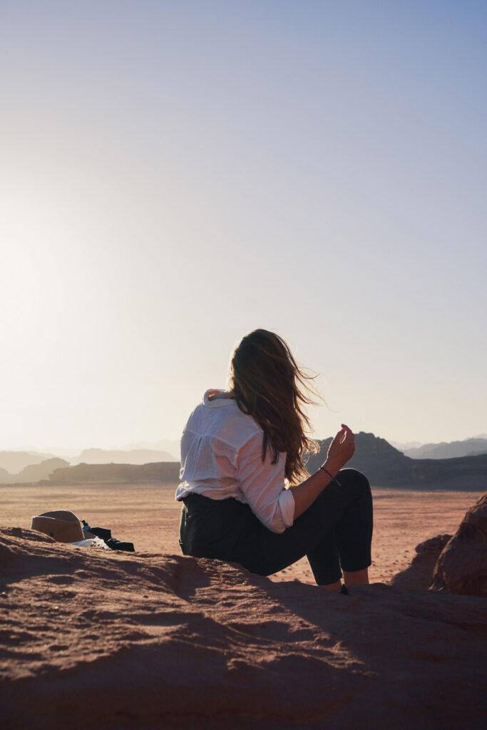 Girl sitting in front of the sunset in Wadi Rum Desert