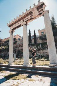 Girl standing underneath a Greek Arch