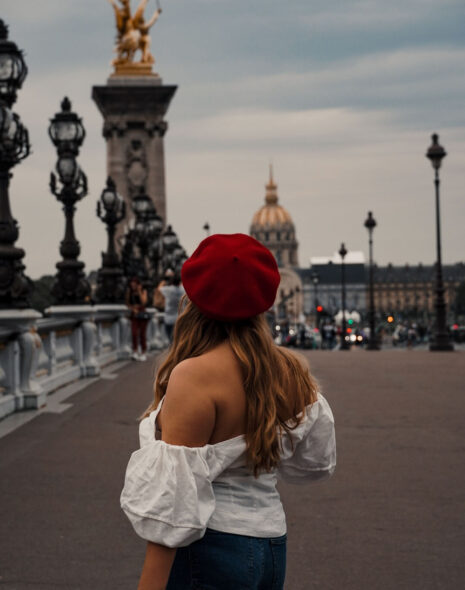 Weekend in Paris - Pont Alexandre III. I am wearing a white shoulder free blouse and a red beret, a perfect outfit for Paris. In the background is the dome of Invalides and the golden details of the bridge.